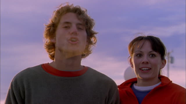 Medium shot young man and woman looking at their breath in cold air outdoors