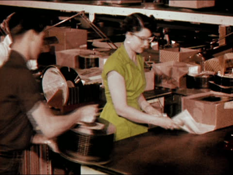 1956 medium shot young man bringing box of records and record sleeves to woman in factory/ woman polishing records/ audio - cat's eye glasses stock videos and b-roll footage