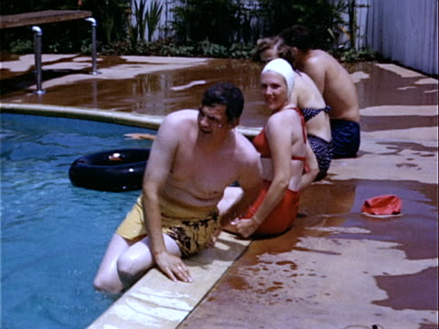 1952 medium shot young man getting out of swimming pool and sitting with two young women and another man at edge of pool / beverly hills, california, usa  - 1952 stock videos & royalty-free footage