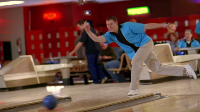 stockvideo's en b-roll-footage met medium shot young man in blue team jersey bowling and cheering w/teammates - bowlen