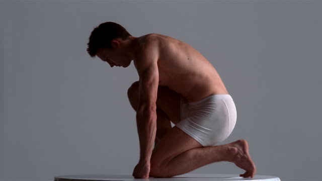 medium shot young man in underwear kneeling on spinning turntable / london - underwear stock videos & royalty-free footage