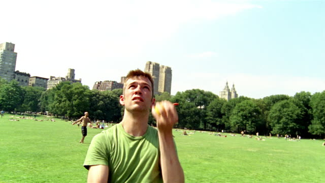 medium shot young man juggling oranges in central park / bouncing orange off cam / new york city - jonglieren stock-videos und b-roll-filmmaterial