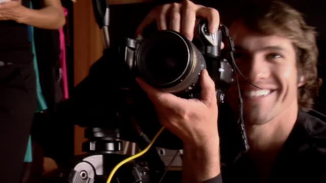 medium shot young man posing for photographer and dancing in studio - 2000s style点の映像素材/bロール