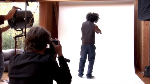 medium shot young man posing for photographer and dancing in studio - kamera blitzlicht stock-videos und b-roll-filmmaterial