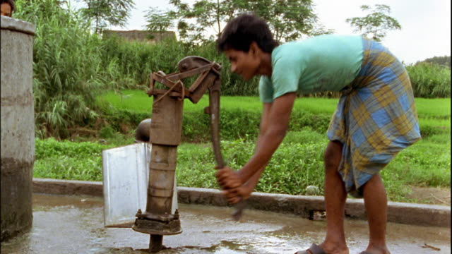 medium shot young man pumping water from well / nepal - vattenpump bildbanksvideor och videomaterial från bakom kulisserna