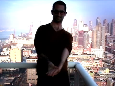 medium shot young man standing on balcony demonstrating flexibility by popping arms out of joint and rotating them, cityscape in background/ new york city - nur junge männer stock-videos und b-roll-filmmaterial