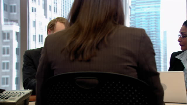 medium shot young man talking and shuffling papers during business meeting in board room/ pan woman passing paper to man at end of table/ new york, new york - shuffling stock videos and b-roll footage