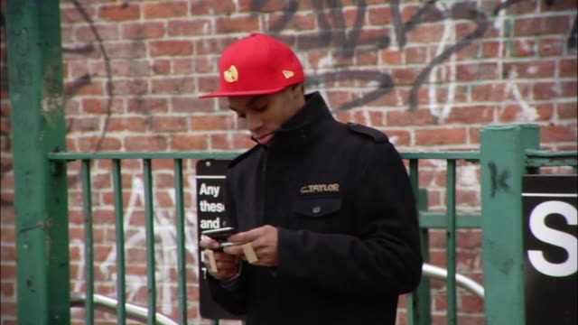 medium shot young man using electronic organizer near city subway sign / new york city, new york, usa - electronic organizer stock videos and b-roll footage