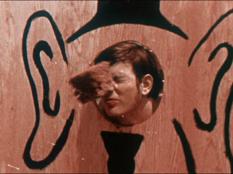 1970 medium shot young man with head sticking out of board in fair booth getting hit in face w/ sponge - fairground stock videos and b-roll footage