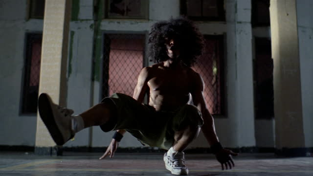 Medium shot young man with large Afro break dancing / Jakarta, Indonesia