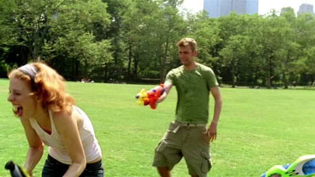 medium shot young men and woman playing with squirt guns in central park / new york city - squirt gun stock videos and b-roll footage