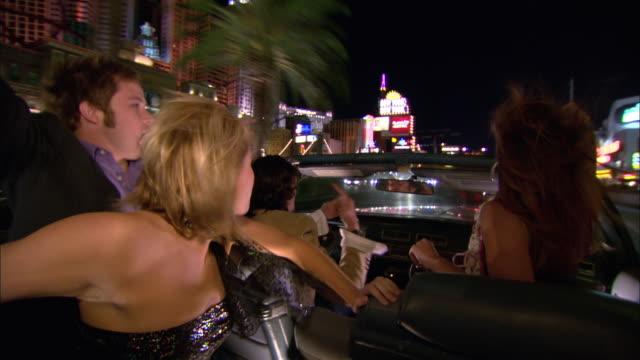 medium shot young men and women driving in convertible down the strip at night/ las vegas, nevada, usa - över axel perspektiv bildbanksvideor och videomaterial från bakom kulisserna