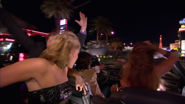 medium shot young men and women driving in convertible down the strip at night/ las vegas, nevada, usa - strapless stock videos & royalty-free footage