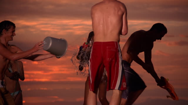 vídeos y material grabado en eventos de stock de medium shot young men and women shooting waterguns + throwing buckets of water at each other / south africa - manguera