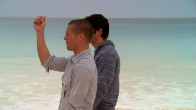 Medium shot Young men talking and walking along beach/ Harbor Island, Bahamas