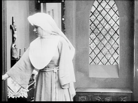 1916 b/w medium shot young nun entering room and looking out window - 1916 stock videos & royalty-free footage