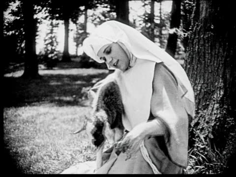 1916 b/w medium shot young nun hugging and feeding goat in garden - innocenza video stock e b–roll