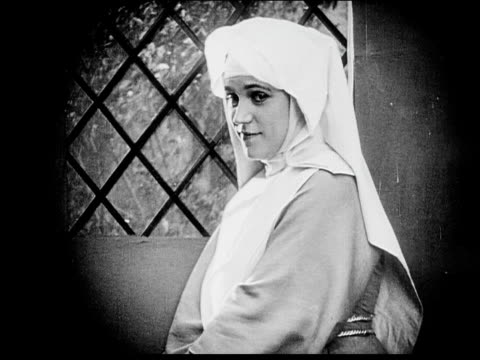 1916 b/w medium shot young nun looking out window and smiling - 1916 stock videos & royalty-free footage