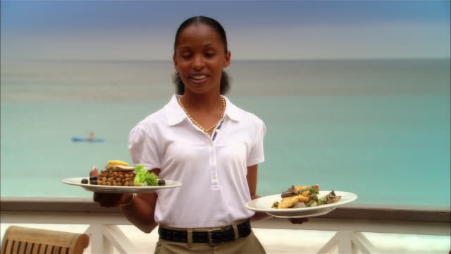 Medium shot Young waitress holding plates of food at seaside restaurant/ Harbor Island, Bahamas