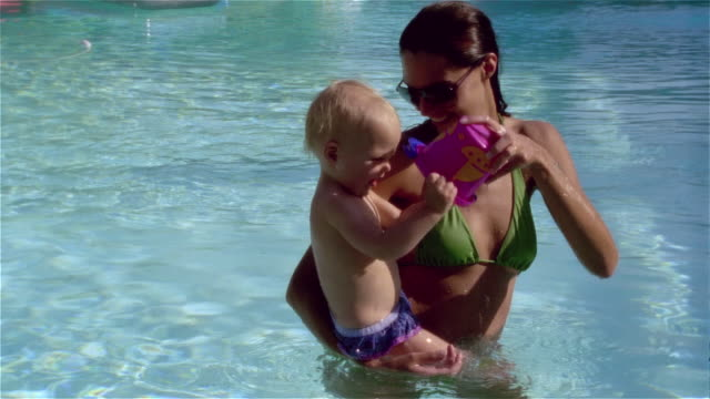 medium shot young woman and baby playing with bucket in swimming pool/ saint-ferme, france - braunes haar stock-videos und b-roll-filmmaterial