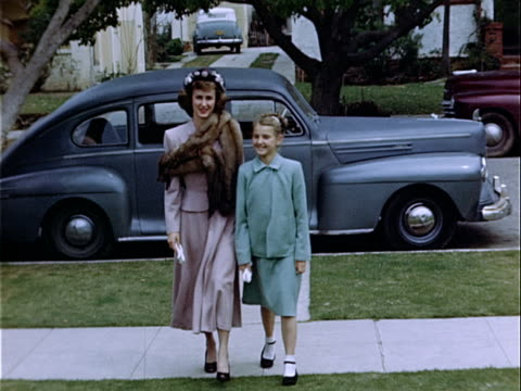 stockvideo's en b-roll-footage met 1949 medium shot young woman and girl walking side by side up sidewalk near lincoln zephyr / los angeles, california, usa  - voetgangerspad
