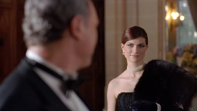 medium shot young woman and older man in eveningwear looking at each other / rack focus man smiling at cam - 年の差カップル点の映像素材/bロール