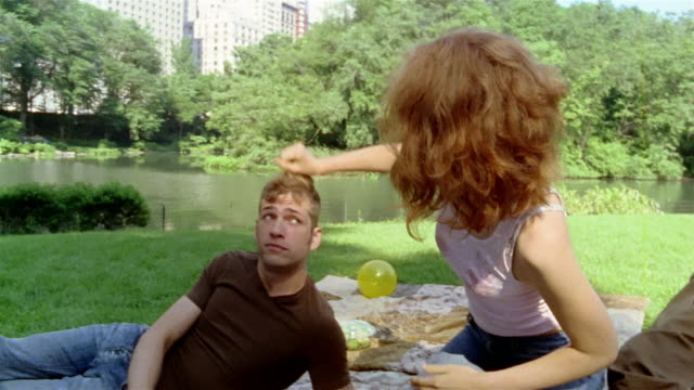 medium shot young woman and two young men on blanket in central park/ woman playing with man's hair/ new york - human hair stock videos & royalty-free footage