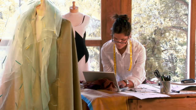 Medium shot young woman clothing designer working on laptop and taking off glasses/ Santa Fe, New Mexico