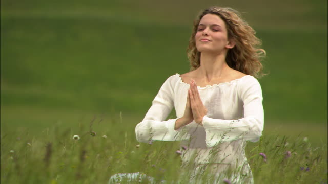 Medium shot young woman doing yoga meditation in field/ Norcia