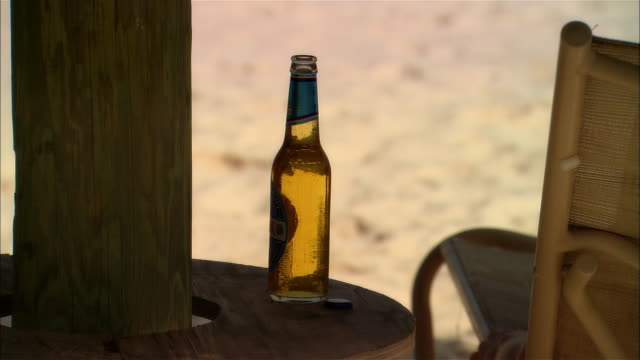 stockvideo's en b-roll-footage met medium shot young woman drinking beer on beach during vacation/ harbor island, bahamas - reiken