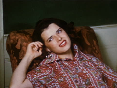 1951 medium shot young woman high on heroin sitting in chair / rolling eyes and touching hair
