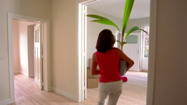 Medium shot young woman holding plant and walking into empty room w/boxes + red carpet in background