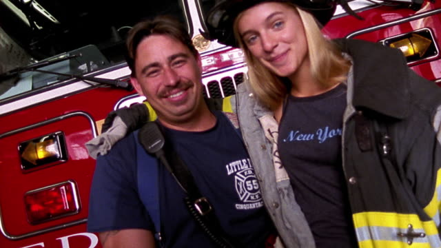 Medium shot young woman in 'New York' T-shirt and firefighter gear posing with firefighter in fire station . NYC