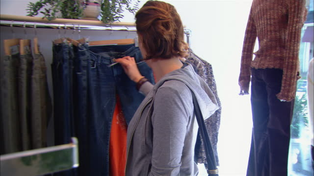 medium shot young woman looking at jeans on rack in clothing shop/ westfield, new jersey - jeans stock videos & royalty-free footage