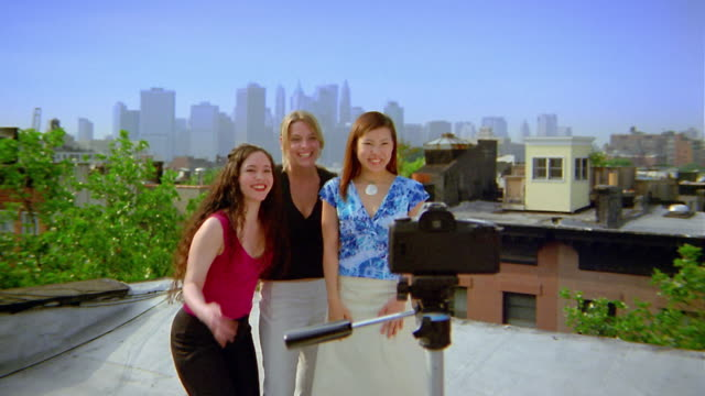 medium shot young woman looking through camera/moving into group shot and making v sign / nyc skyline in background - 2003年点の映像素材/bロール
