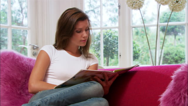 medium shot young woman on sofa reading magazine/ london - comfortable stock videos & royalty-free footage