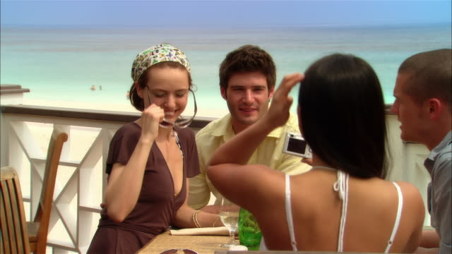 medium shot young woman photographing friends at seaside restaurant during vacation/ harbor island, bahamas - パティオ点の映像素材/bロール