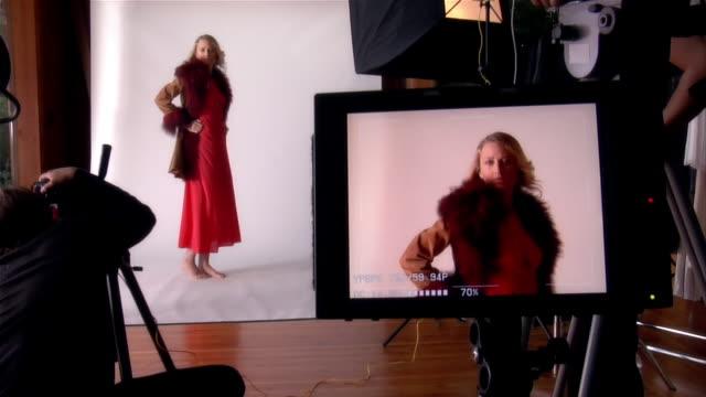 Medium shot young woman posing for photographer in studio