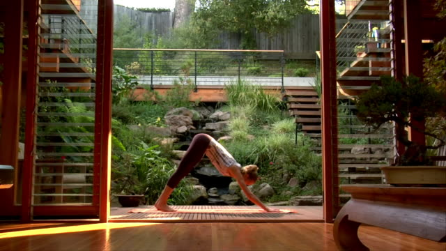 medium shot young woman practicing yoga on patio deck/ california, usa - sun salutation stock videos & royalty-free footage