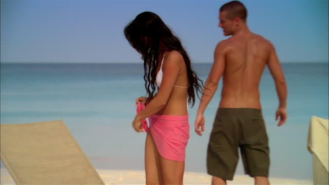 stockvideo's en b-roll-footage met medium shot young woman removing sarong and walking with young man on beach near surf during vacation/ harbor island, bahamas - sarong
