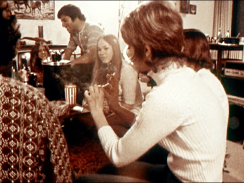 1971 medium shot young woman seated on floor with others taking hit of marijuana and passing it on/ california/ audio - smoking issues stock videos & royalty-free footage