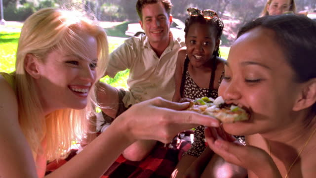 medium shot young woman sharing slice of pizza with friend at picnic / griffith park / los angeles, california - picnic stock videos & royalty-free footage