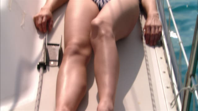 stockvideo's en b-roll-footage met medium shot young woman sunbathing on sailboat deck/ harbor island, bahamas - haarband