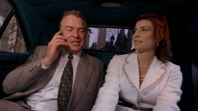 medium shot young woman talking on phone in back of limousine/ handing phone to older man / taking phone back - 年の差カップル点の映像素材/bロール