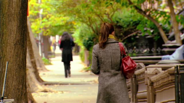 Medium shot young woman walking down treelined street/ Brooklyn, New York