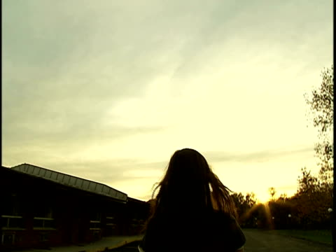 Medium shot Young woman with long brown hair floating across empty parking lot at sunset