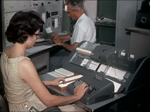 1962 medium shot young woman working at cardpunch machine and man working at desk in background / audio - machinery stock videos & royalty-free footage