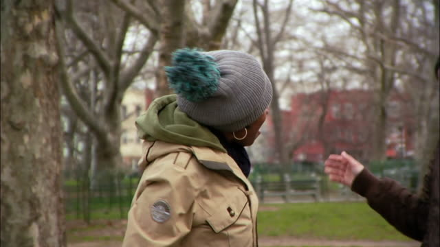 vídeos y material grabado en eventos de stock de medium shot young women giving each other street handshakes in park / williamsburg, brooklyn, new york, usa - cuello parte de la vestimenta