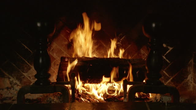 Medium shot Yule log burning in hearth