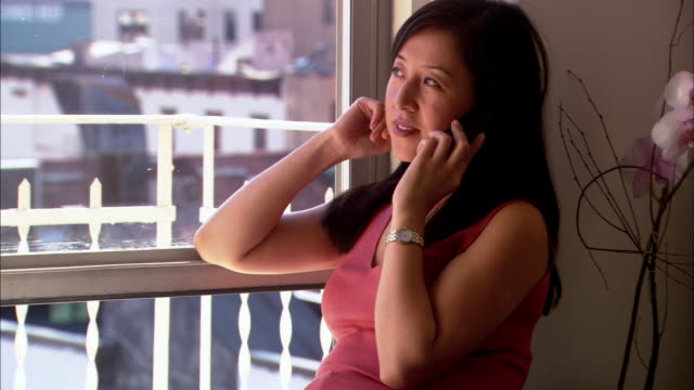 vídeos de stock e filmes b-roll de medium shot zoom in asian woman sitting on windowsill and talking on telephone - peitoril de janela
